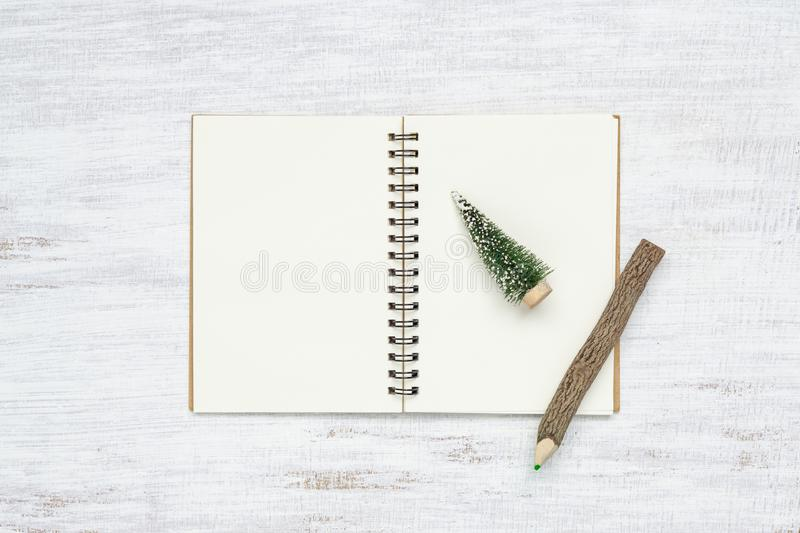 Top view of blank  notebook with mini christmas tree and pencil on grunge white wood  background. Mockup Christmas background with royalty free stock image