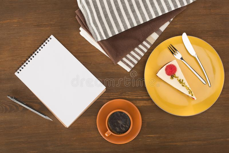 top view of blank notebook with pen, gourmet cake and cup of coffee stock photography