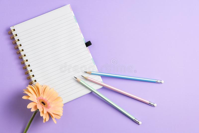 Top view of blank notebook with pencils and flower on purple pastel background royalty free stock photo