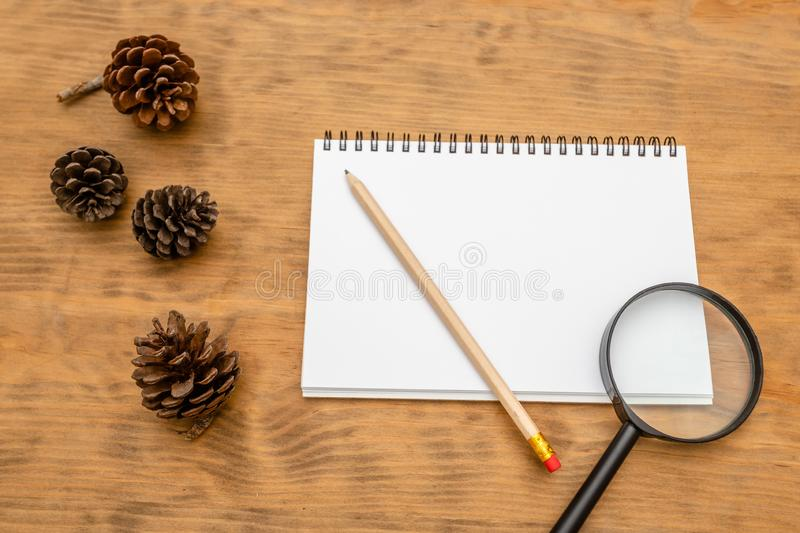 Top view of Blank notebook white paper and magnifying glass on brown wooden background with space for your message stock photography