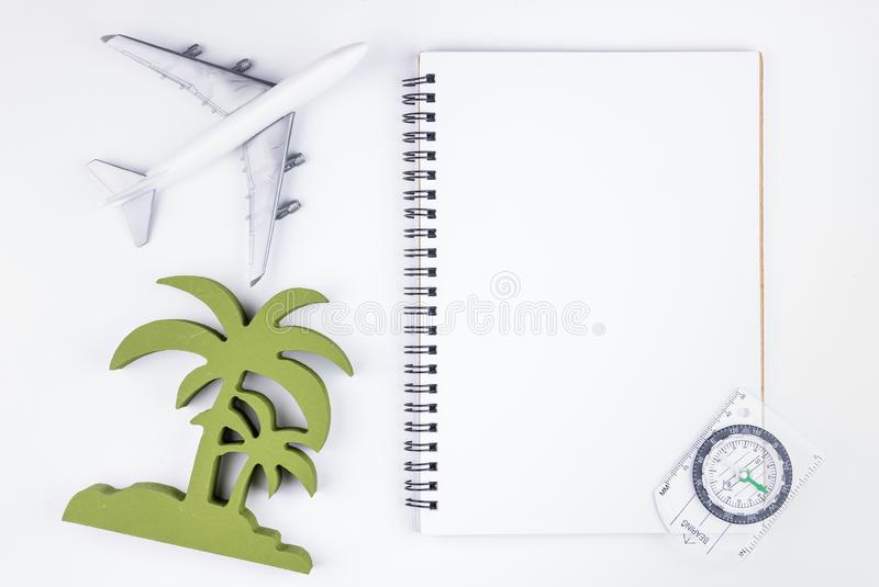 Top view of Blank notebook white paper and passenger plane on on. White background with copy space for your message.Business travel transportation system royalty free stock image