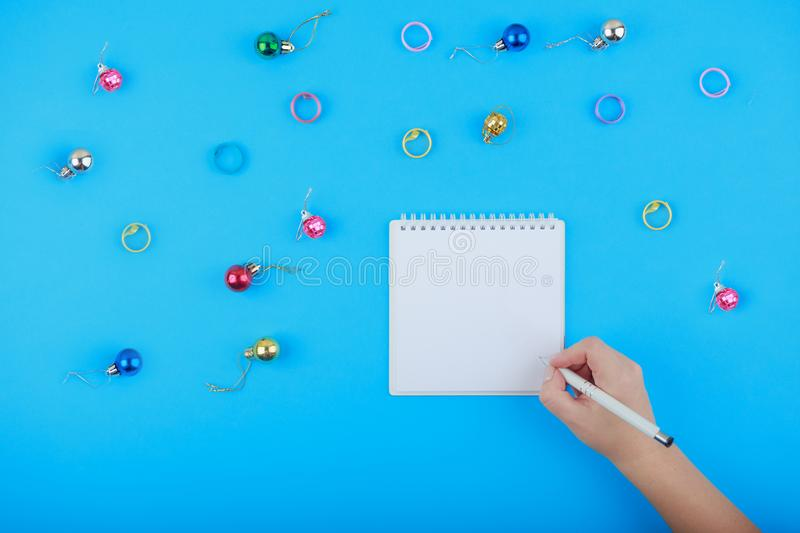 Top view of blank notebook and woman hand with pen, free space. Girl writing to do list, copy space. Flat lay royalty free stock images