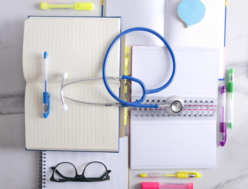 Top view of blank notebooks, stationary, glasses and stethoscope.Concept of medical exam preparation. Top vie of open notebook, paper for notes,  markers and royalty free stock photo