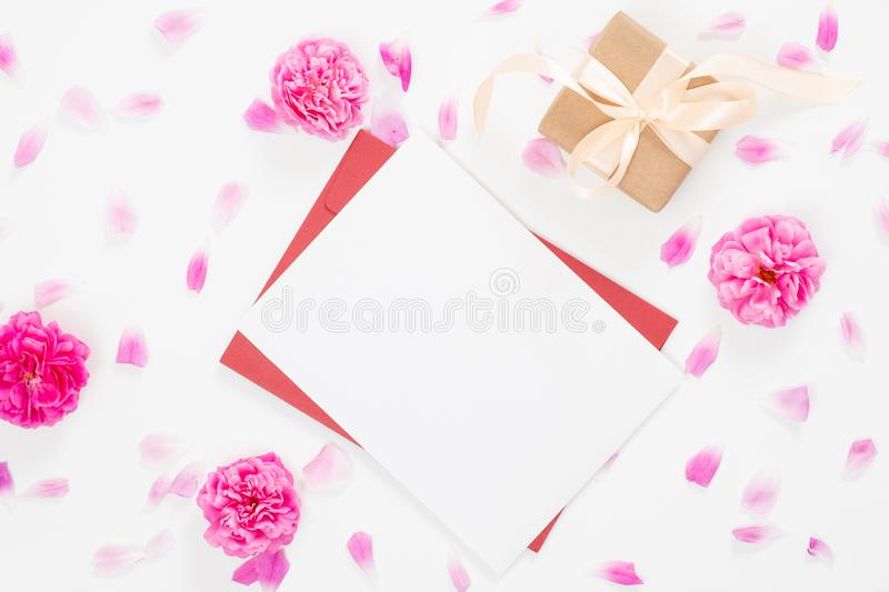 Top view blank paper card, red envelope, gift box, rose flowers buds and petals on white background. Minimal flat lay style stock image