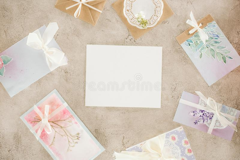 Top view of blank paper surrounded with greeting cards. On concrete surface royalty free stock photo