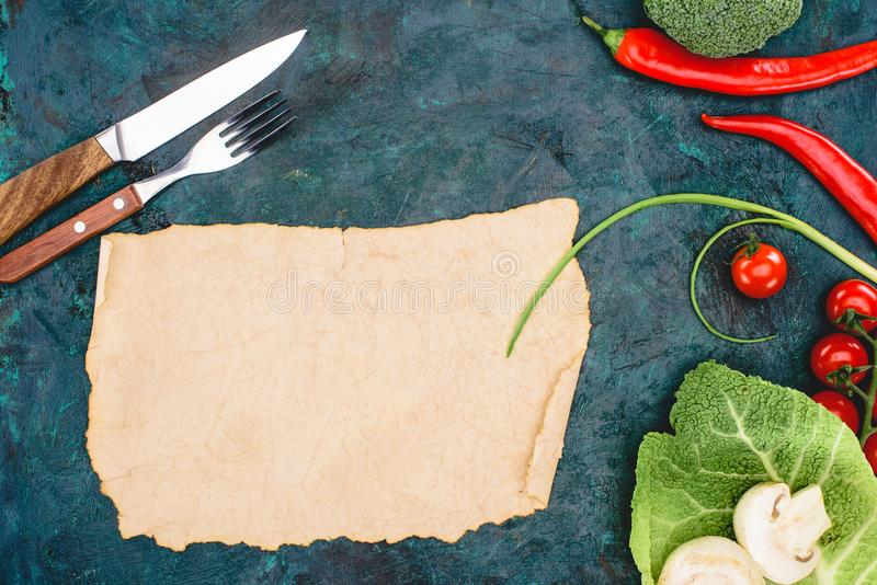 Top view of blank parchment, fork with knife and ripe raw vegetables royalty free stock image