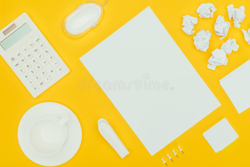 Top view of blank sheet of paper, crumpled papers, notes, calculator and computer mouse. Isolated on yellow stock photo