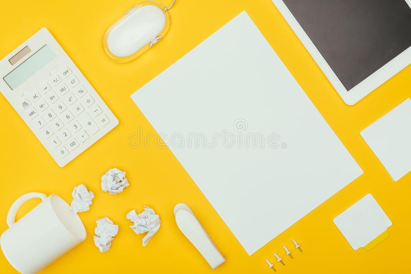 Top view of blank sheet of paper, crumpled papers, notes, calculator and cup. Isolated on yellow stock photos