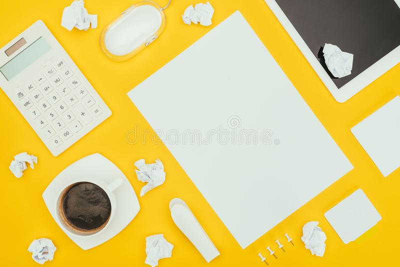 Top view of blank sheet of paper, crumpled papers, notes, calculator and digital tablet. Isolated on yellow stock image