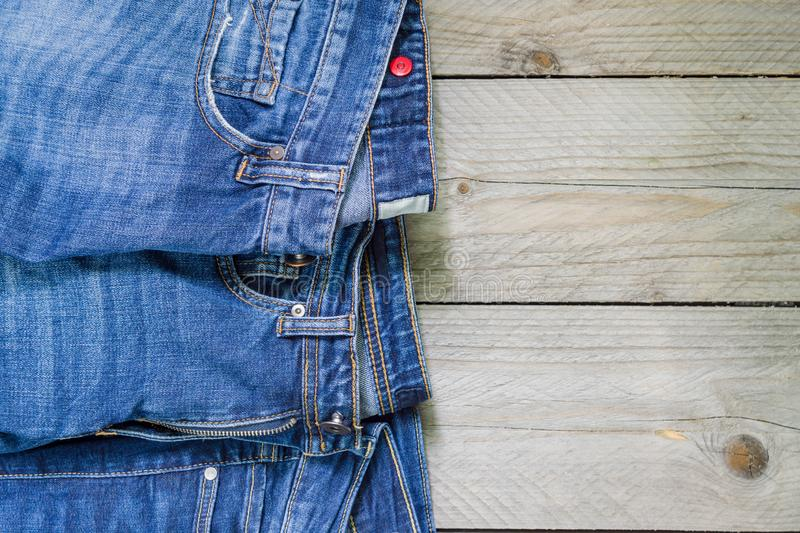 Top view of blue denim jeans arranged on wooden background. Beauty and fashion clothing concept stock photo