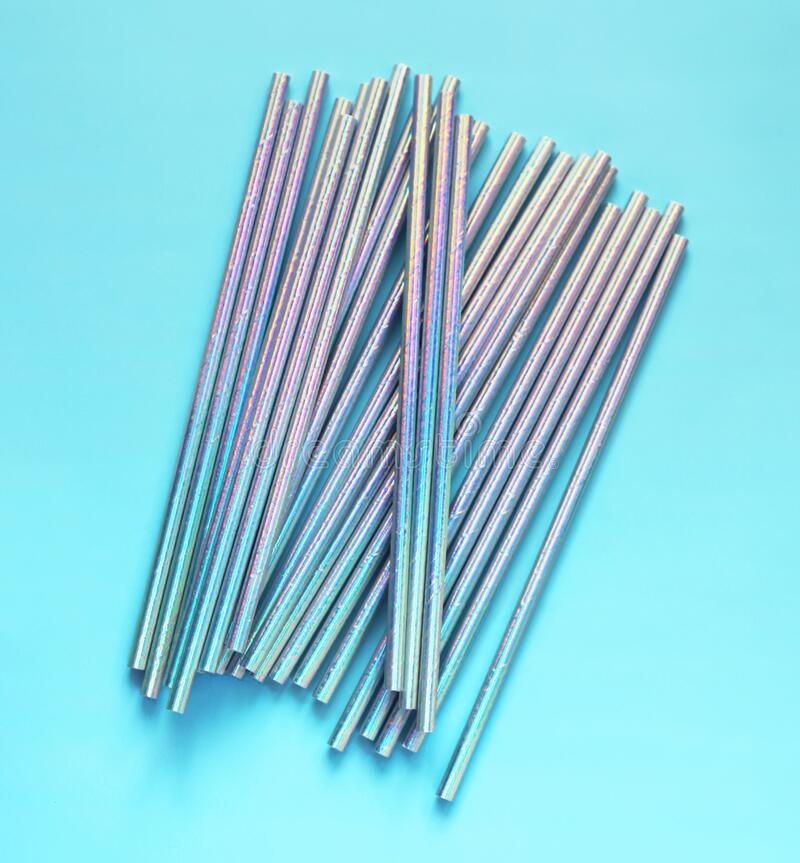 Top view of blue glisten paper disposable eco-friendly straws. Drinking straws for party on blue background. Eco waste concept stock image
