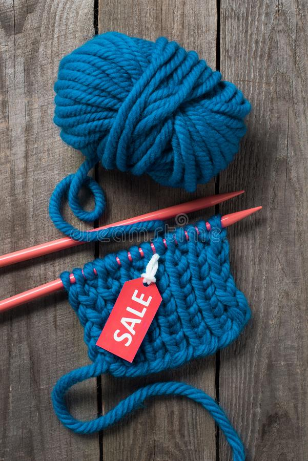 top view of blue knitting needles blue yarn ball and sale tag stock photo