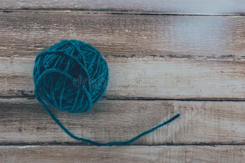 Top view of blue knitting yarn ball. On wooden background royalty free stock image