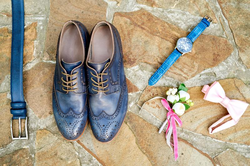 Top view of blue leather groom shoes, watches, belt, boutonniere, pink bowtie on brown natural stone. Groom wedding accessories. royalty free stock image