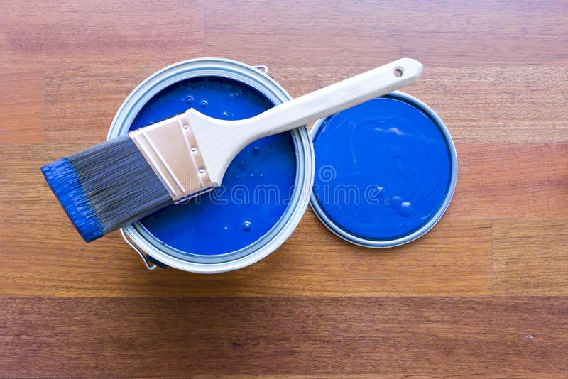 Top View of Blue House Paint Can and Brush. Top view of blue paint can and brush on top with cherry hardwood floor background royalty free stock image