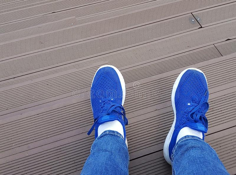 Top view of blue sneakers shoes standing on wooden floor stock photos