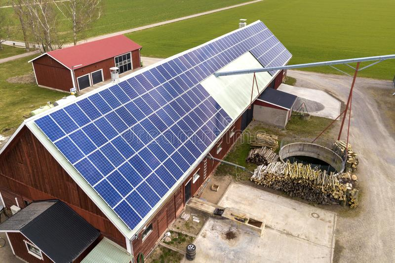 Top view of blue solar photo voltaic panels system on wooden building, barn or house roof. Renewable ecological green energy. Production concept royalty free stock photography