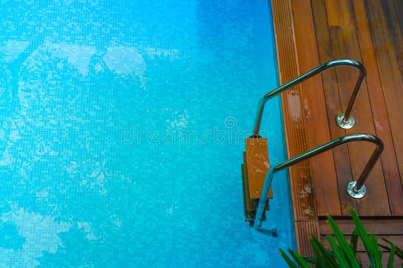 Top view of blue water in swimming pool with grab bars ladder surrounded with wooden floor and green trees. Selective focus stock image