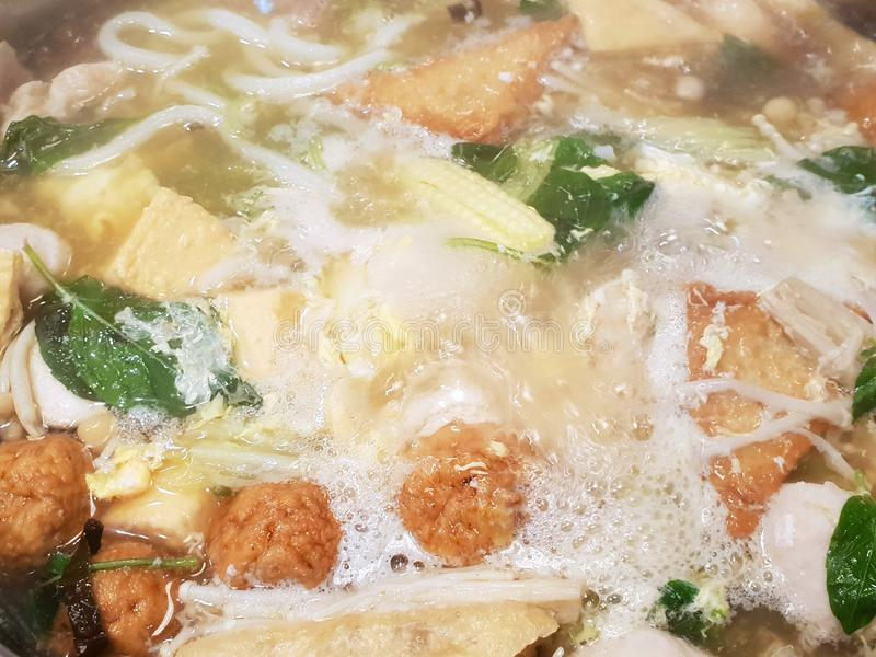 Top view of boiled fish ball and vegetavle in hot pot as a background royalty free stock images