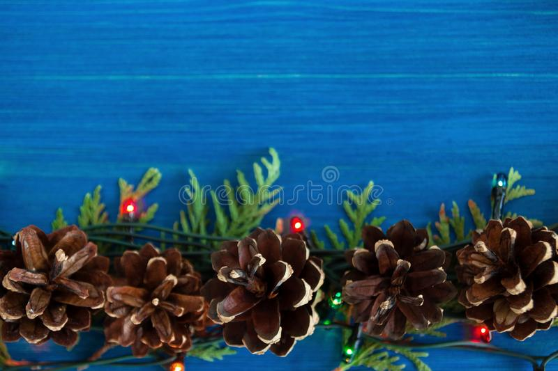 Top view on border from Christmas lights, fir branches and pine cones on the blue wooden background. Top view on border from Christmas lights, fir branches and royalty free stock photography