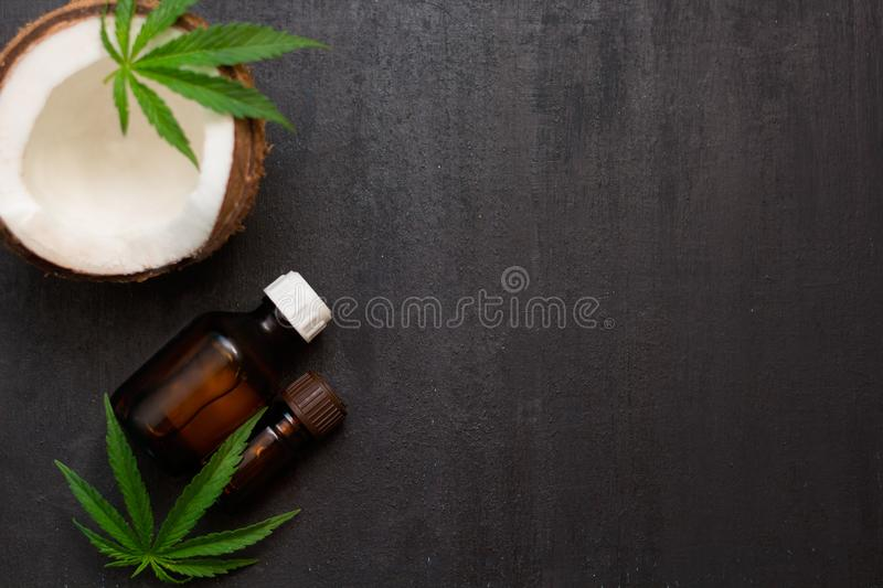 Top view bottles with coconut and cannabis oils with half of coconut. And hemp leaves royalty free stock photography