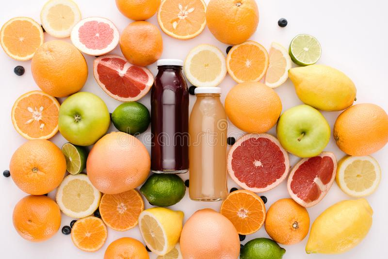 Top view of bottles of fresh juice with ripe citrus fruits slices. On white surface stock photography