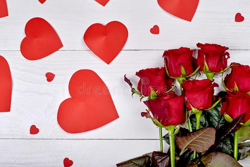 Top view bouquet of red roses and paper hearts on white wooden b royalty free stock image