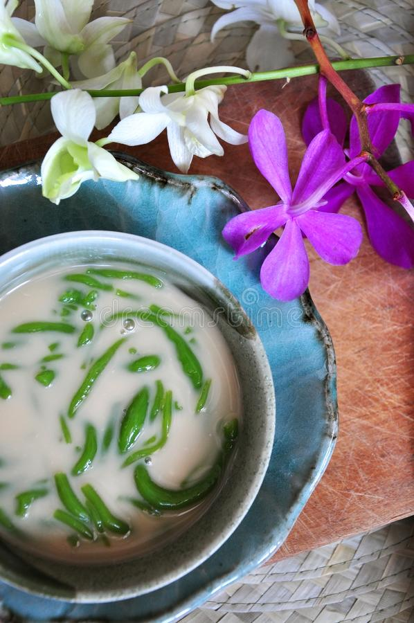Top view of Cendol Bowl with Orchid. Top view bowl of traditional dessert Cendol decorated with orchid on background stock image