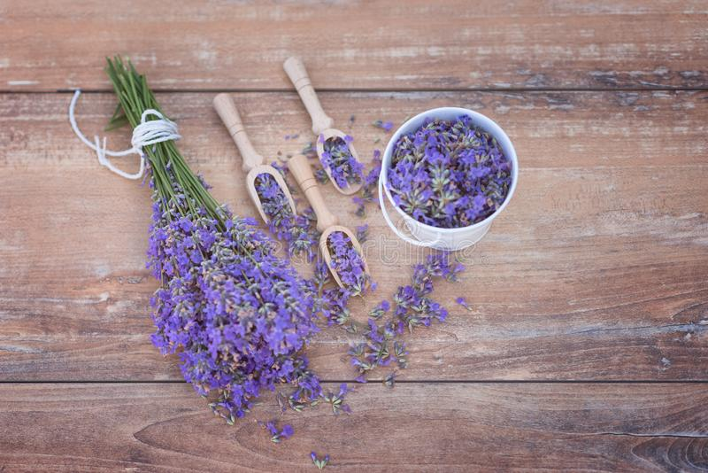 Top view of a bowl and wooden spoons with fresh lavender flowers and a bouquet of lavender. On a brown wooden background royalty free stock photo
