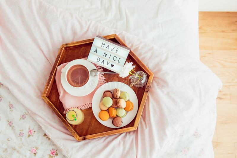 Top view Breakfast in bed with Have a nice day text on lighted box. Cup of coffee, juice, macaroons, flower in vase on wooden tray. Good morning mood royalty free stock photos