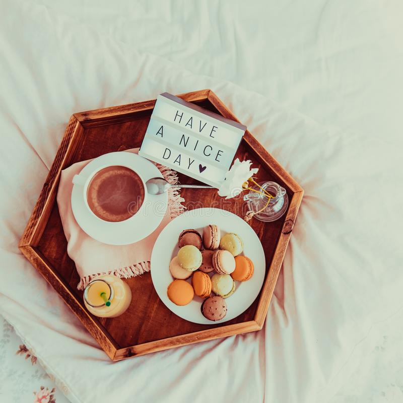 Top view Breakfast in bed with Have a nice day text on lighted box. Cup of coffee, juice, macaroons, flower on wooden tray. Good. Morning mood. Hospitality stock photos