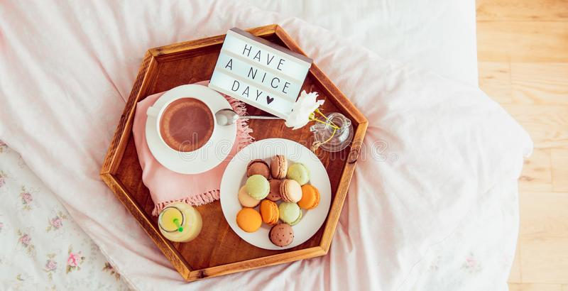 Top view Breakfast in bed with Have a nice day text on lighted box. Cup of coffee, juice, macaroons on wooden tray. Good morning. Mood. Hospitality, care royalty free stock photography