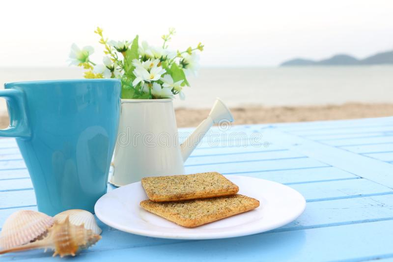 Top view of breakfast, blue cup of hot chocolate and cracker bread on white dish on blue wooden table sea view royalty free stock photos