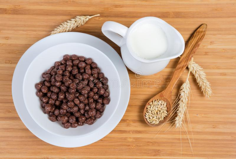 Top view of breakfast cereal chocolate balls and milk. Breakfast cereal chocolate balls in white bowl, milk in the small milk jug among ears and grains in wooden stock image