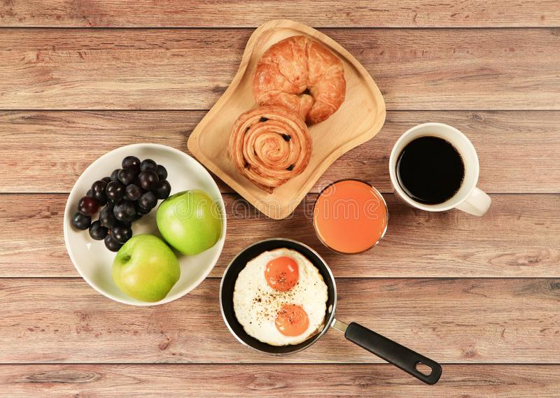 Top view of breakfast set , black coffee , orange juice, fried eggs,danish pastry and croissant, two apples and grape on wooden stock photos