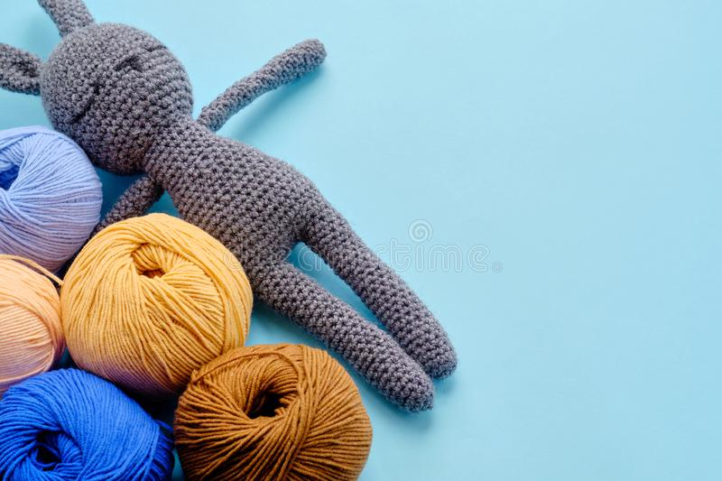 Top view of the bright color yarn clews with grey stuffed amigurumi bunny on the blue background. Concept of amigurumi toy making. Top view of the bright color stock images