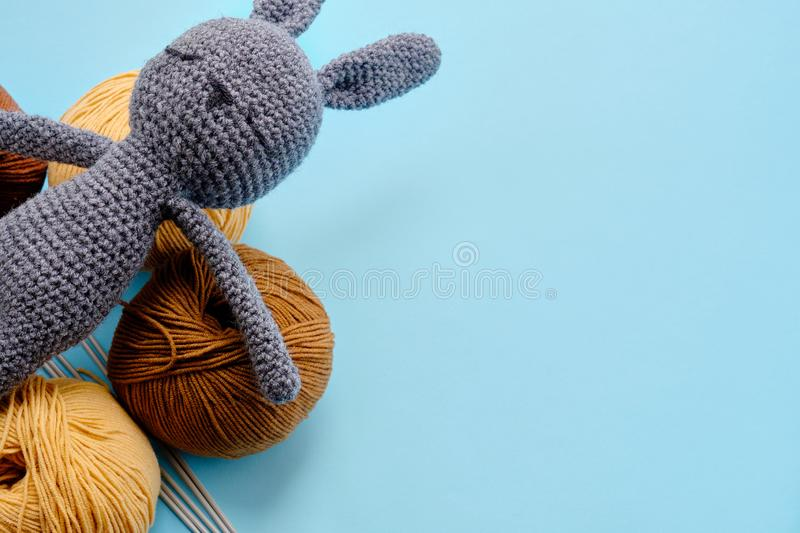 Top view of the bright color yarn clews with grey stuffed amigurumi bunny on the blue background. Concept of amigurumi toy making. Handcrafting, knitting stock photography