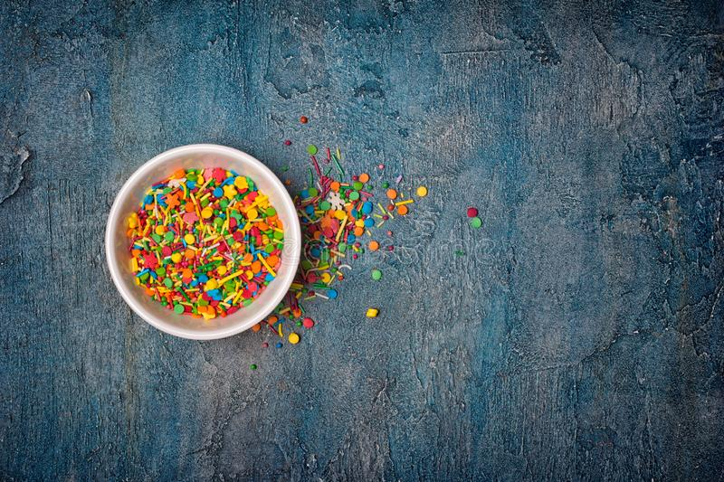 Top view on bright colorful sugar sprinkles or confetti as baking decor. Top view on bright colorful sugar sprinkles or confetti in white bowl as baking decor on stock photos
