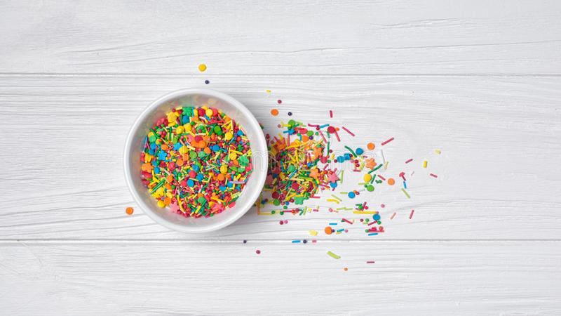 Top view on bright colorful sugar sprinkles or confetti as baking decor. Top view on bright colorful sugar sprinkles or confetti in white bowl as baking decor on stock photo