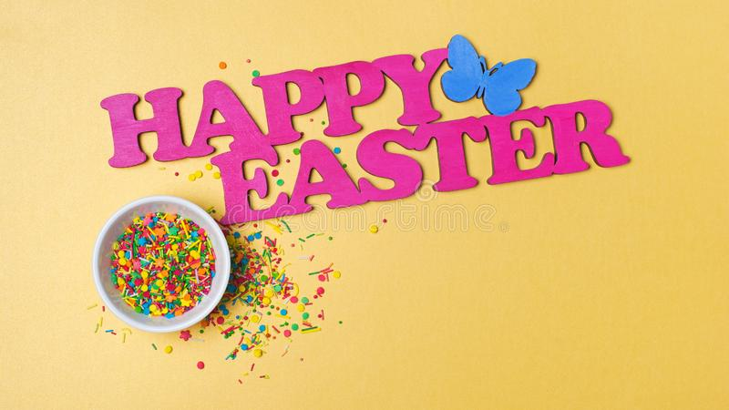 Bright colorful sugar sprinkles or confetti as baking decor with text happy easter. Top view on bright colorful sugar sprinkles or confetti in white bowl as stock photography