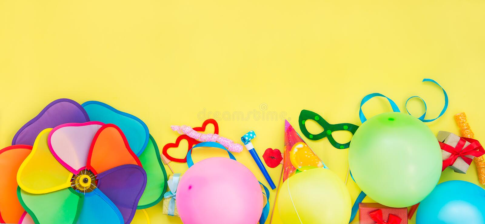 Top view bright party tools and decoration - baloons, funny carnival masks, festive tinsel on yellow background. Happy birthday gr stock photography