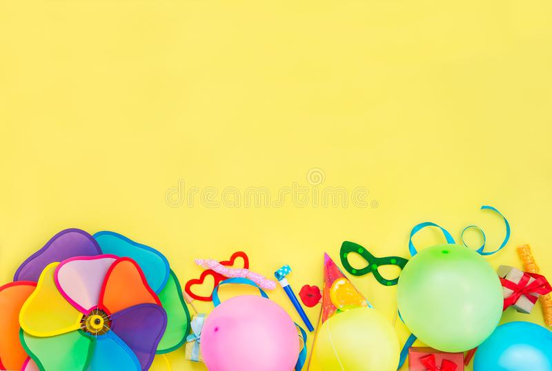 Top view bright party tools and decoration - baloons, funny carnival masks, festive tinsel on yellow background. Happy birthday gr. Eeting card. Design concept stock photos