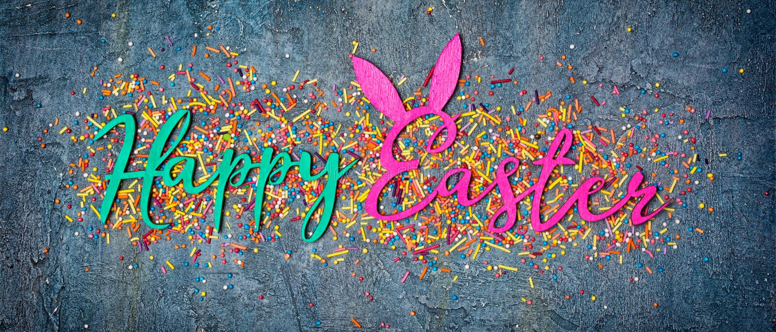 Banner with color text of happy easter and sugar sprinkles or confetti as decor for bakery. Top view on bright text of happy easter with sugar sprinkles or stock photo