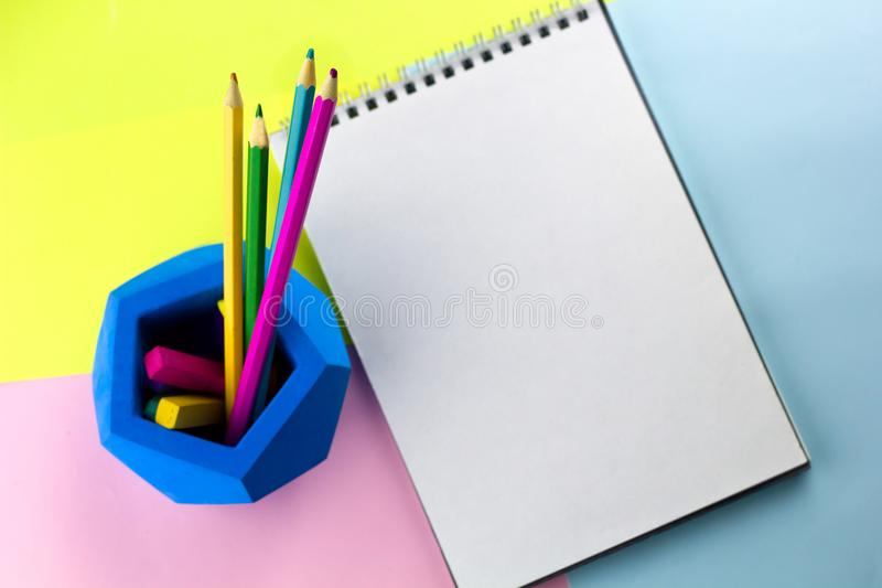 Top view bright working place. Notebook with empty sheetcopy space and bright pencils royalty free stock images