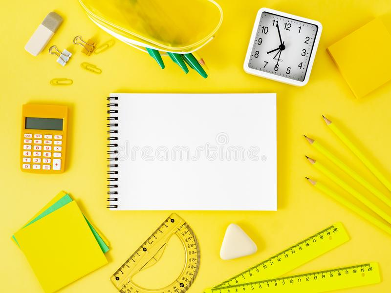Top view of bright yellow office desktop with blank notepad, sch royalty free stock image