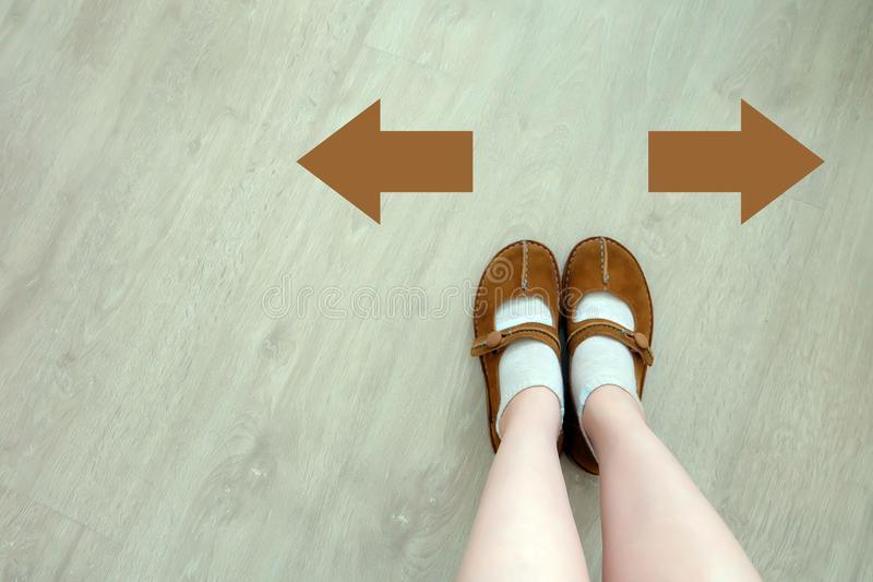 Top View of Brown Boot with Different Brown Decision Arrow. A Pair of Feet Standing. Shoes Walking Direction on Wooden royalty free stock photography