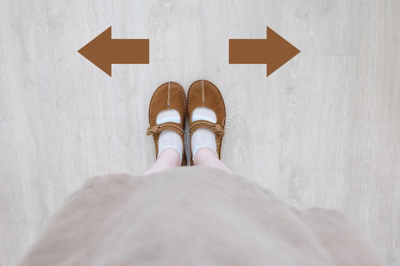 Top View of Brown Boot with Different Brown Decision Arrow. A Pair of Feet Standing. Shoes Walking Direction on Wooden stock images