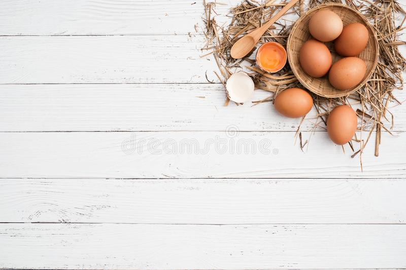 Top view brown chicken egg  in bamboo basket. And egg yolk on the hay with white wooden table background, Flat lay with copy space royalty free stock images