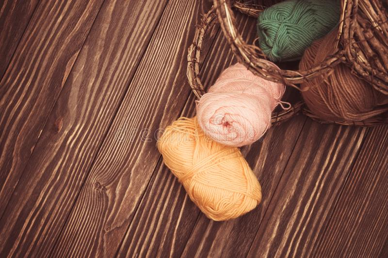 Top view of brown and green pink woolen tangles of threads in wicker basket on wooden knitting background selective focus. Top view of brown and green pink royalty free stock photography