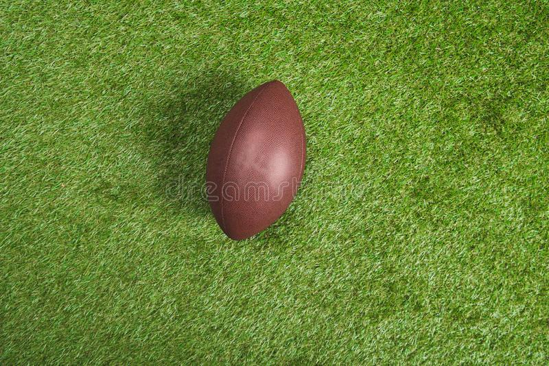 Top view of brown leather rugby ball. On green grass royalty free stock photo